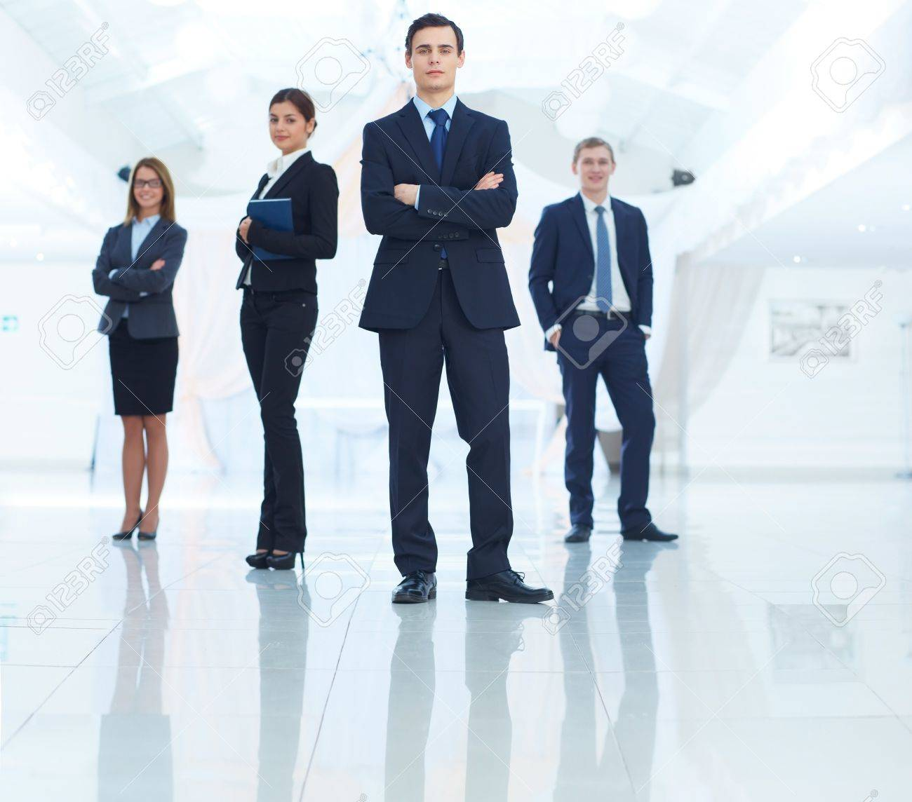 Portrait of young businessman looking at camera with elegant partners on background Stock Photo - 16848850
