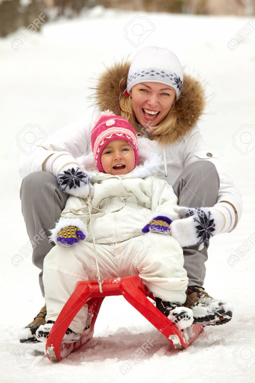 Happy girl and woman in winterwear sitting on sledge in park Stock Photo - 17087696