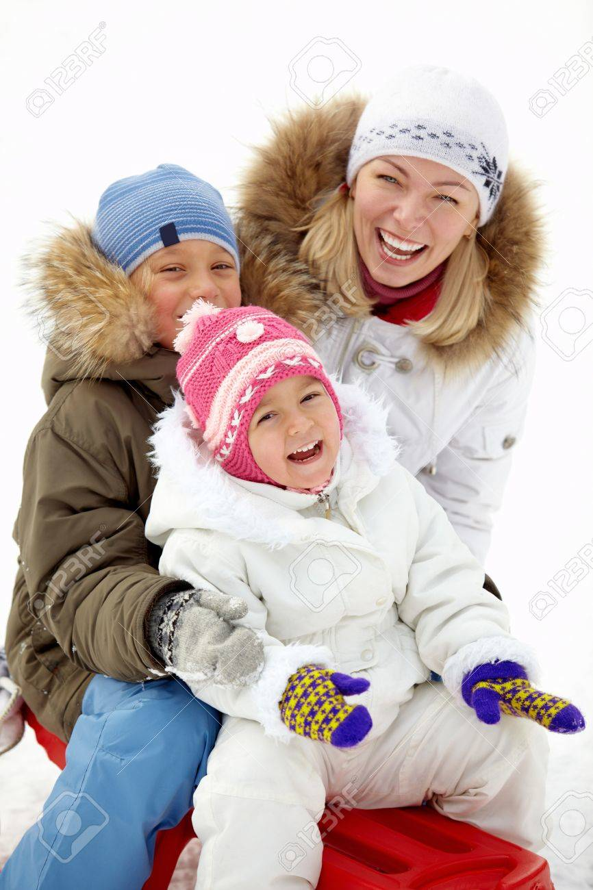 Happy kids and their mother sitting on sledge in park and laughing Stock Photo - 17340550