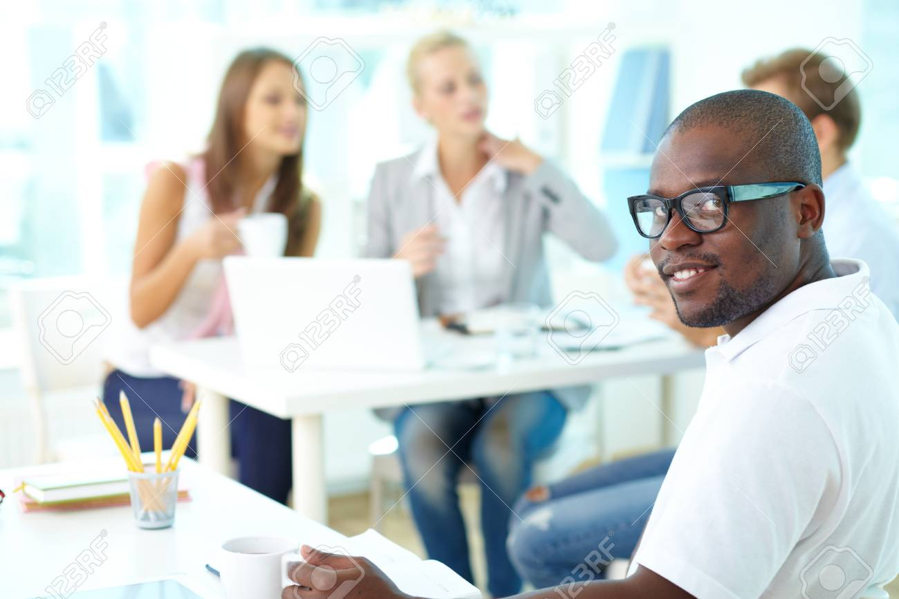 Portrait of happy African guy looking at camera in working environment Stock Photo - 17380771