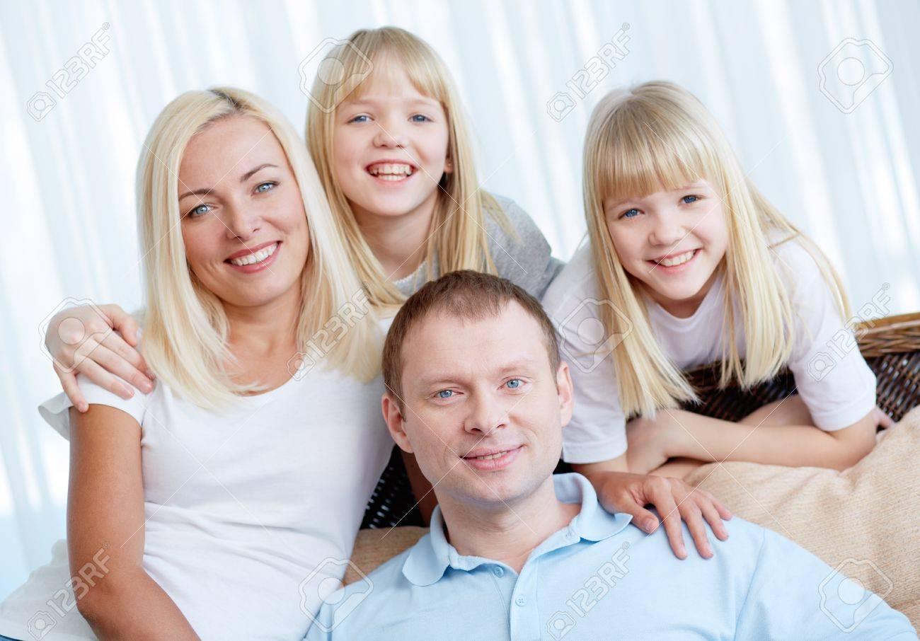 Portrait of happy couple with twin daughters resting at home Stock Photo - 17785620