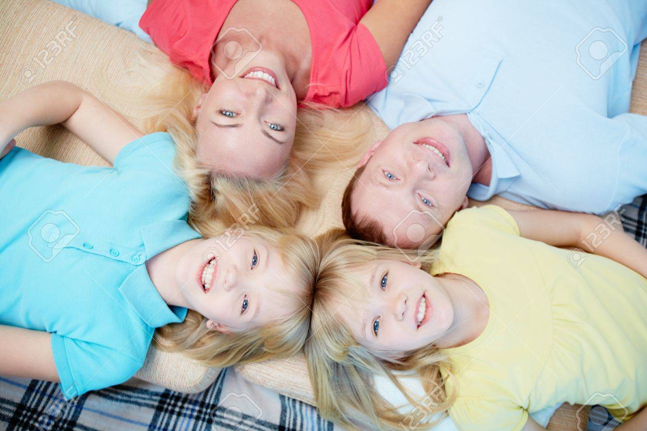 Above angle of happy family of four looking at camera at home Stock Photo - 17785899