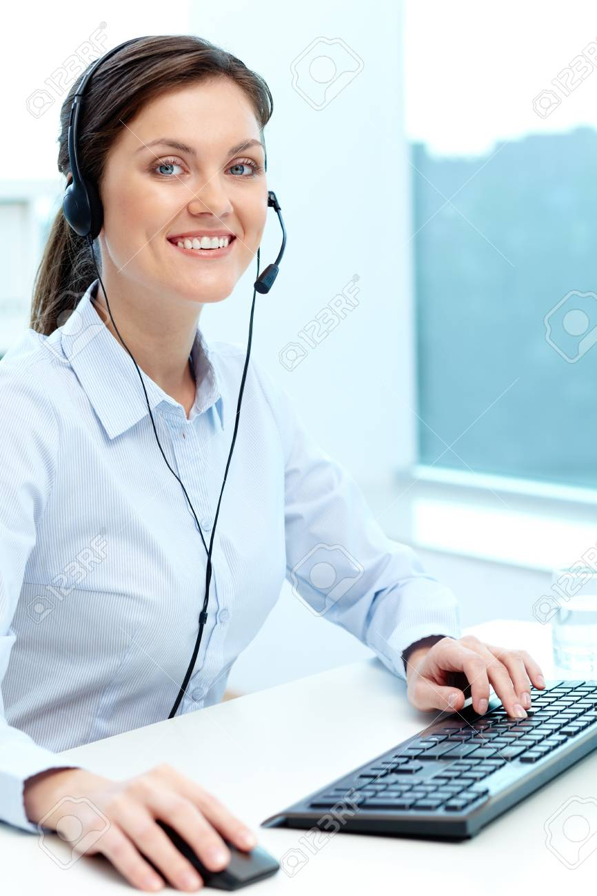 Portrait of young operator with headset looking at camera with friendly smile Stock Photo - 18591139