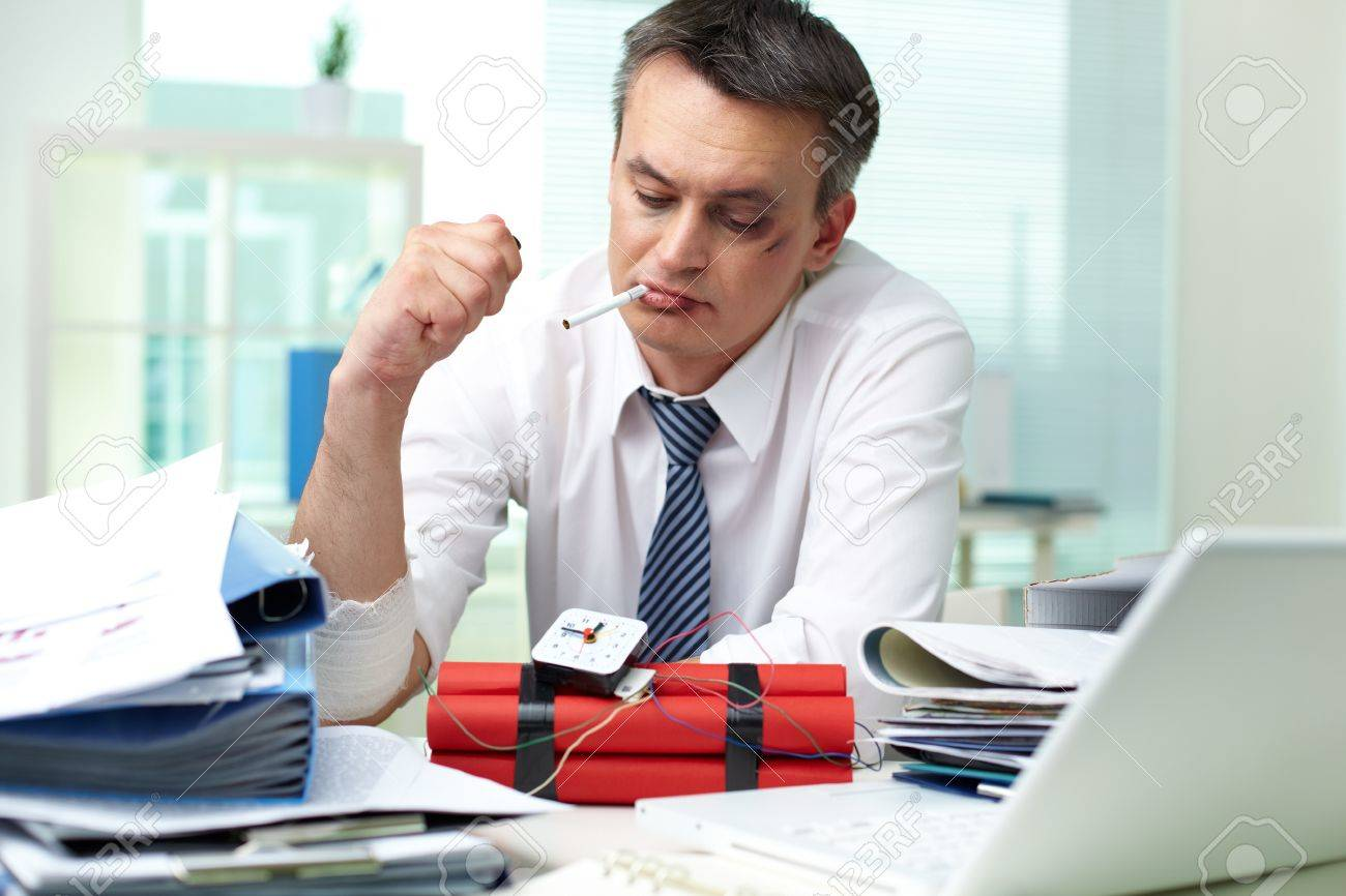 Smoking businessman looking at hand-crafted bomb in office Stock Photo - 19155107