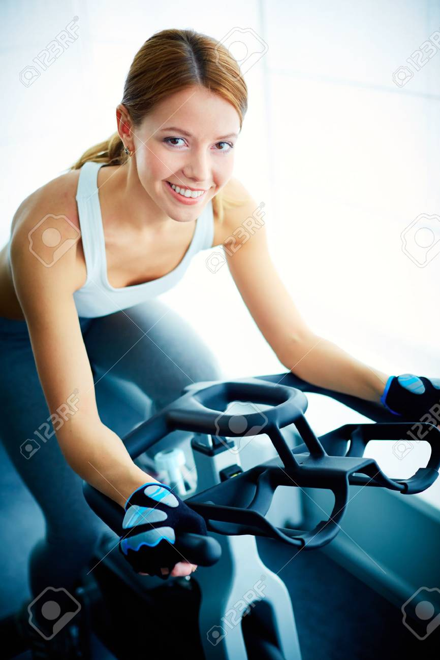 Portrait of young female looking at camera while training on simulator in gym Stock Photo - 20137303