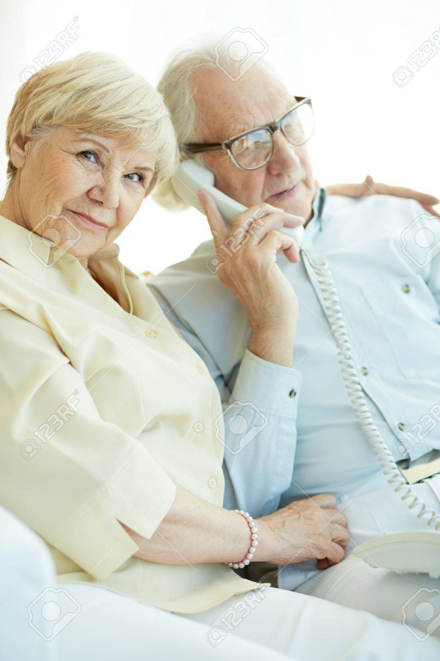 Portrait of elderly woman looking at camera with her husband talking on the phone near by Stock Photo - 20258947