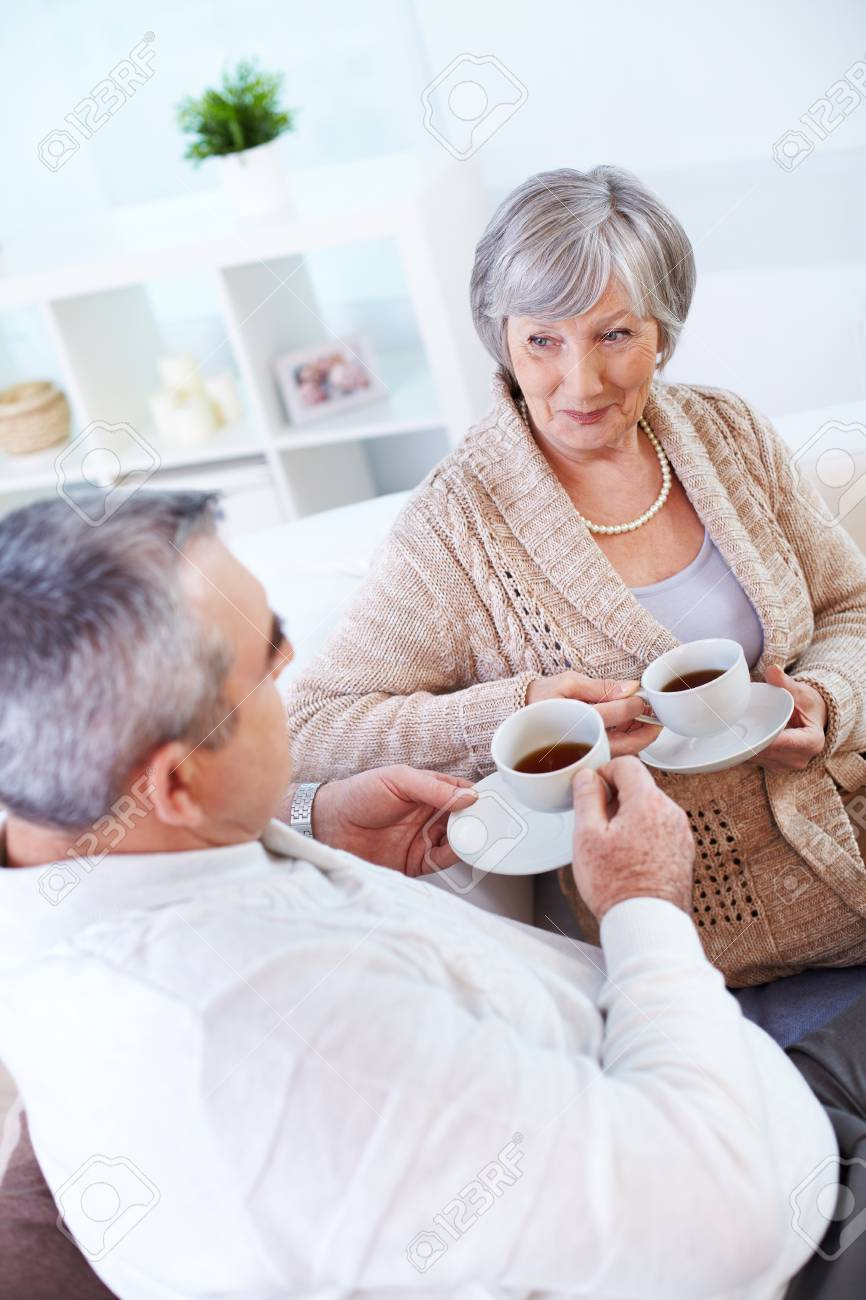 Portrait of mature man and his wife drinking tea and interacting Stock Photo - 22247098