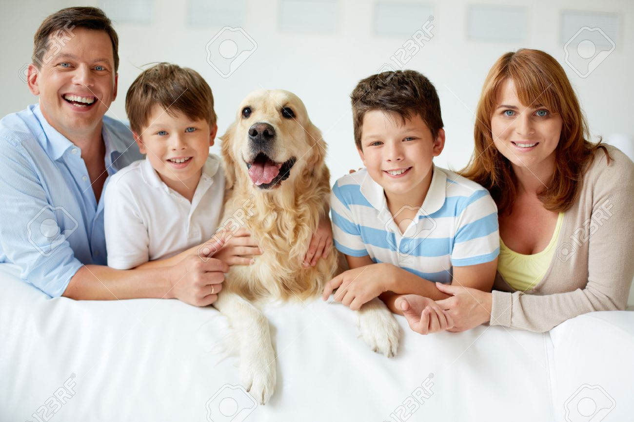 Portrait of happy family with their pet looking at camera Stock Photo - 22247765