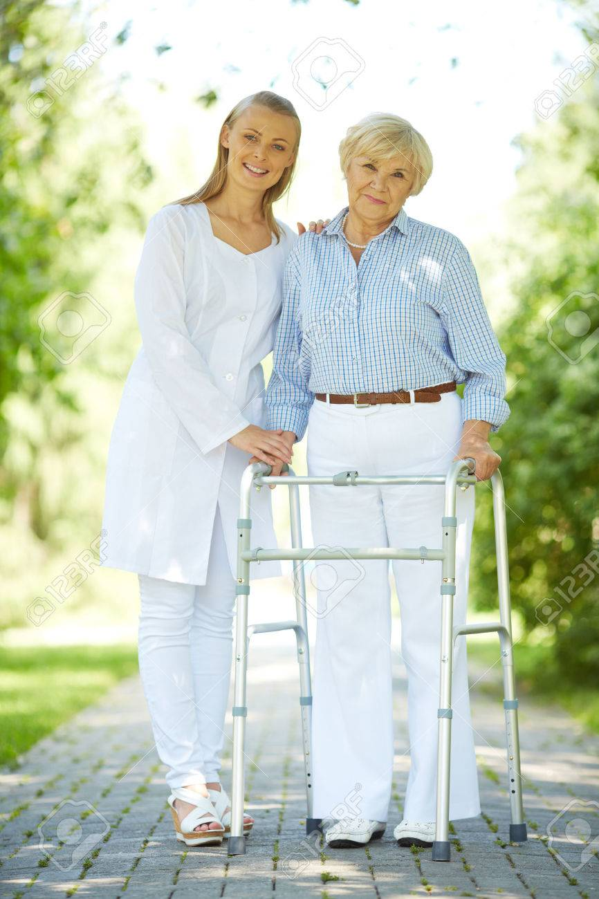 Pretty nurse and senior patient with walking frame looking at camera outside Stock Photo - 22351161