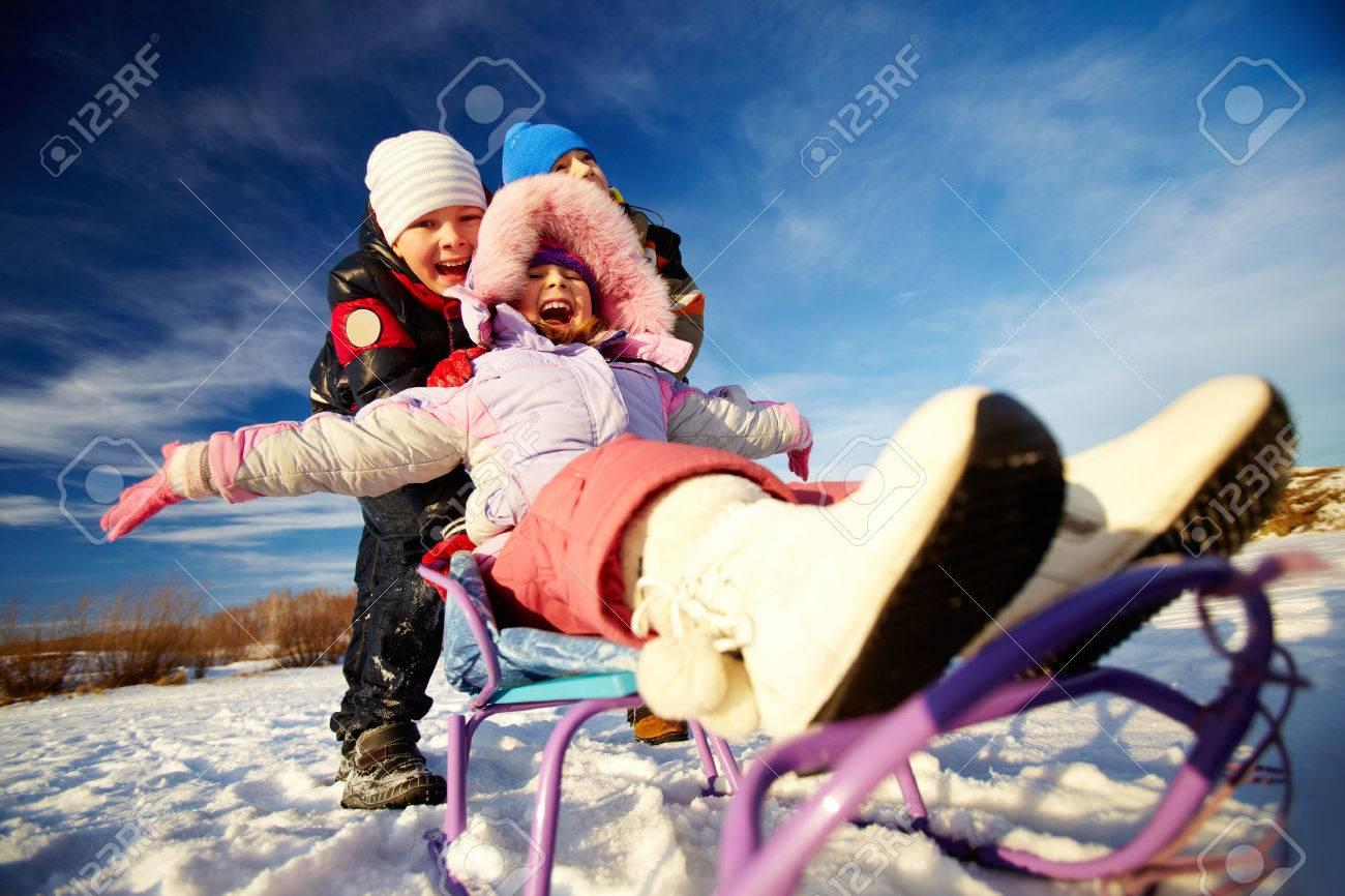 Friendly kids in winterwear riding on sledge outside Stock Photo - 24068797
