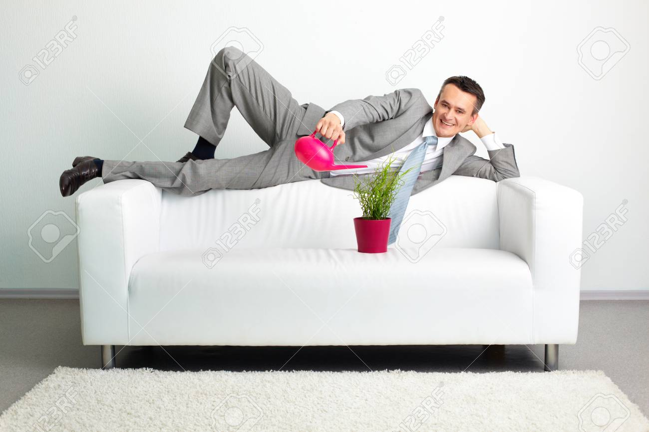 Photo of happy man watering plant while lying on sofa Stock Photo - 25815162