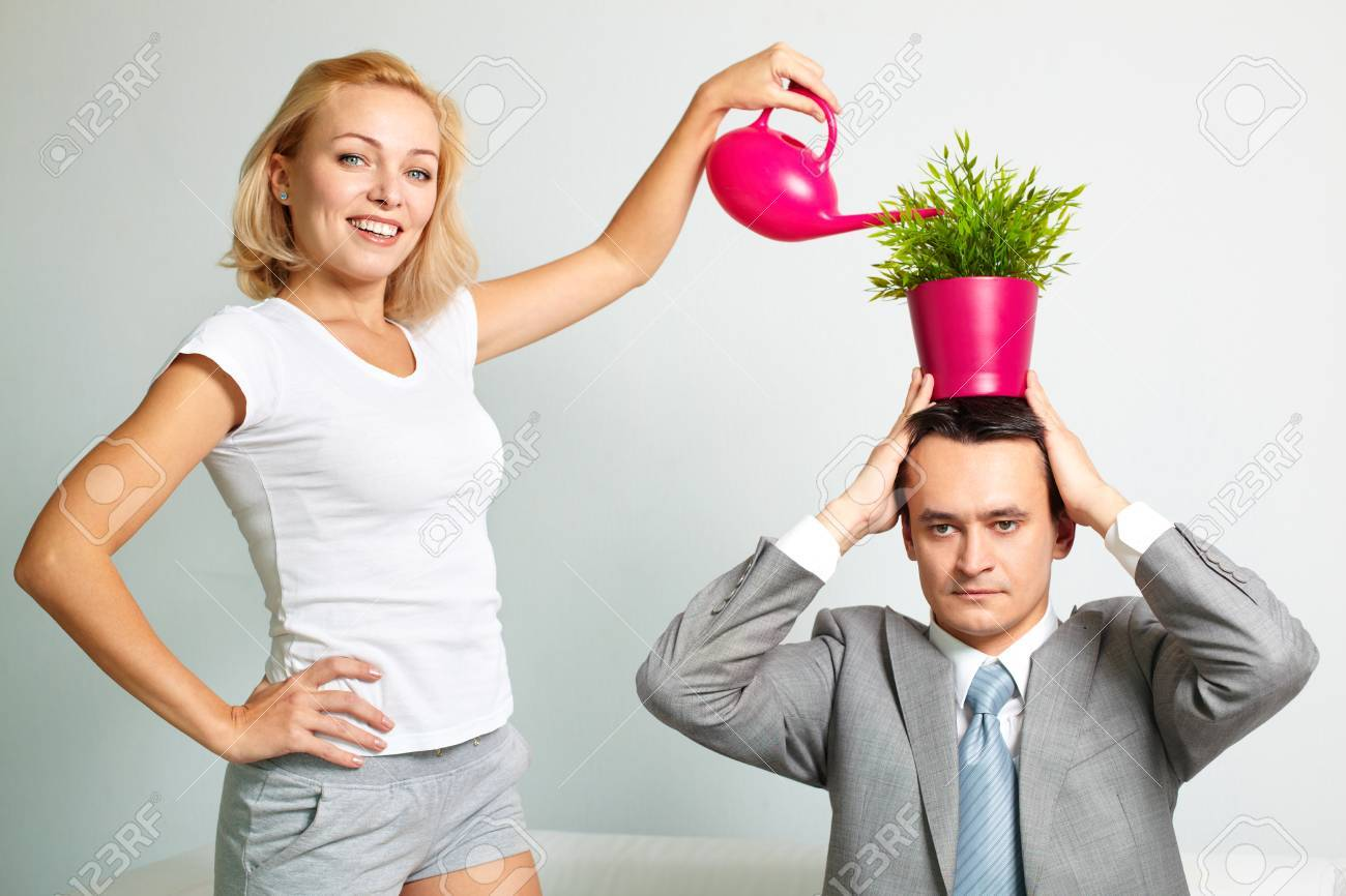 Photo of serious man with plant on head being watered by happy woman Stock Photo - 25815164