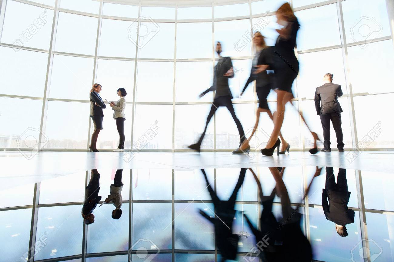 Several white collar workers communicating in office against window with three colleagues walking through near by Stock Photo - 25891380