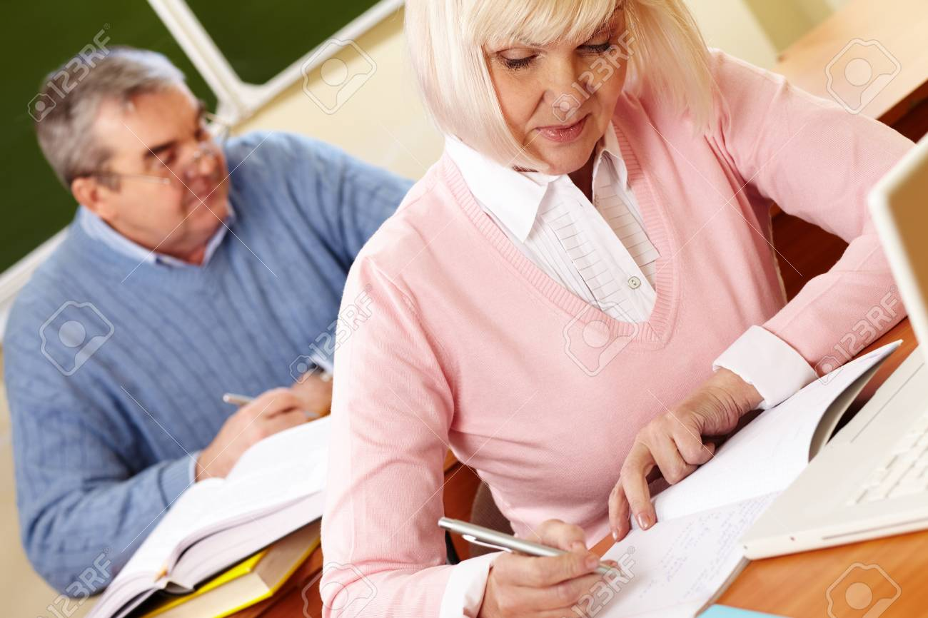 Portrait of mature female making notes in copybook with senior man on background Stock Photo - 28331870
