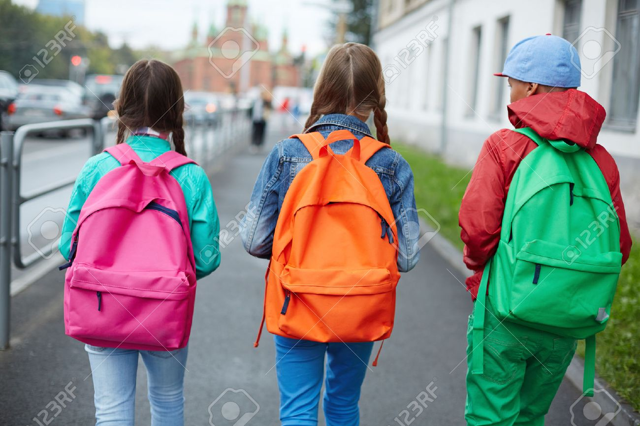 Backs of schoolkids with colorful rucksacks moving in the street Stock Photo - 32134289