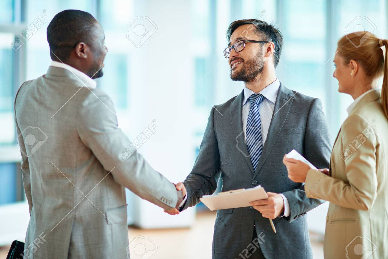Two Businessmen Making Agreement Their Female Colleague Standing