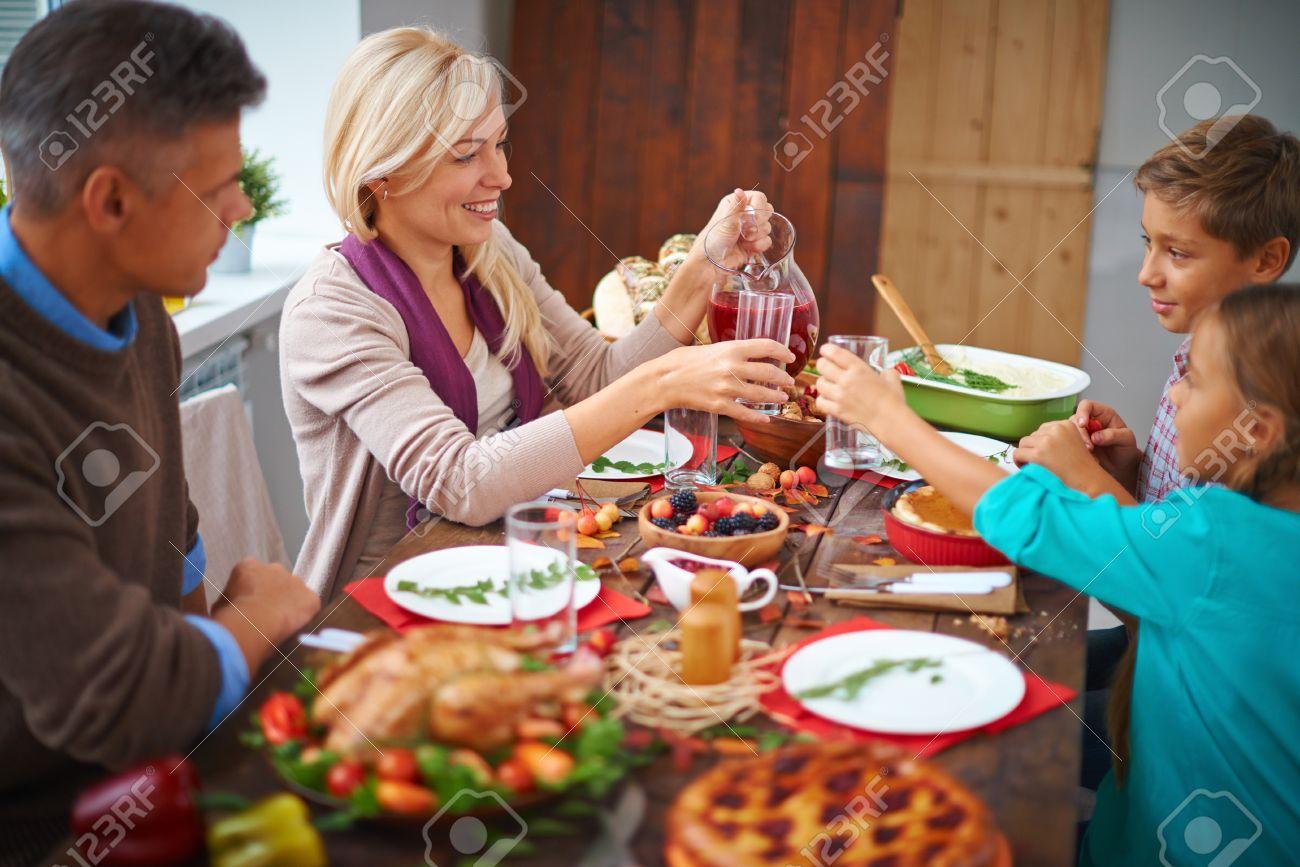 Portrait Of Modern Family Of Four Having Festive Dinner On