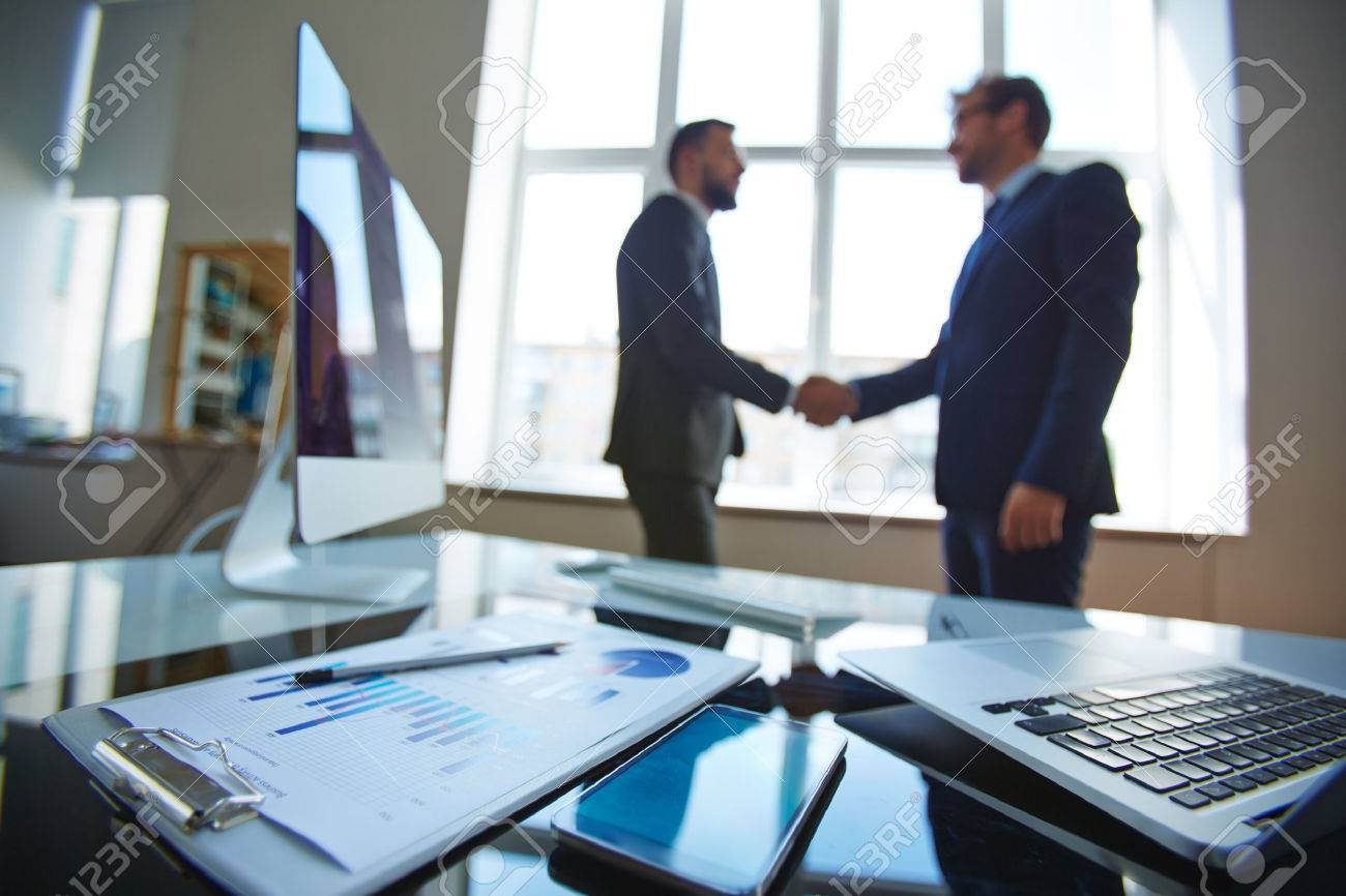 Business objects at workplace with businessmen handshaking on background Stock Photo - 44276748