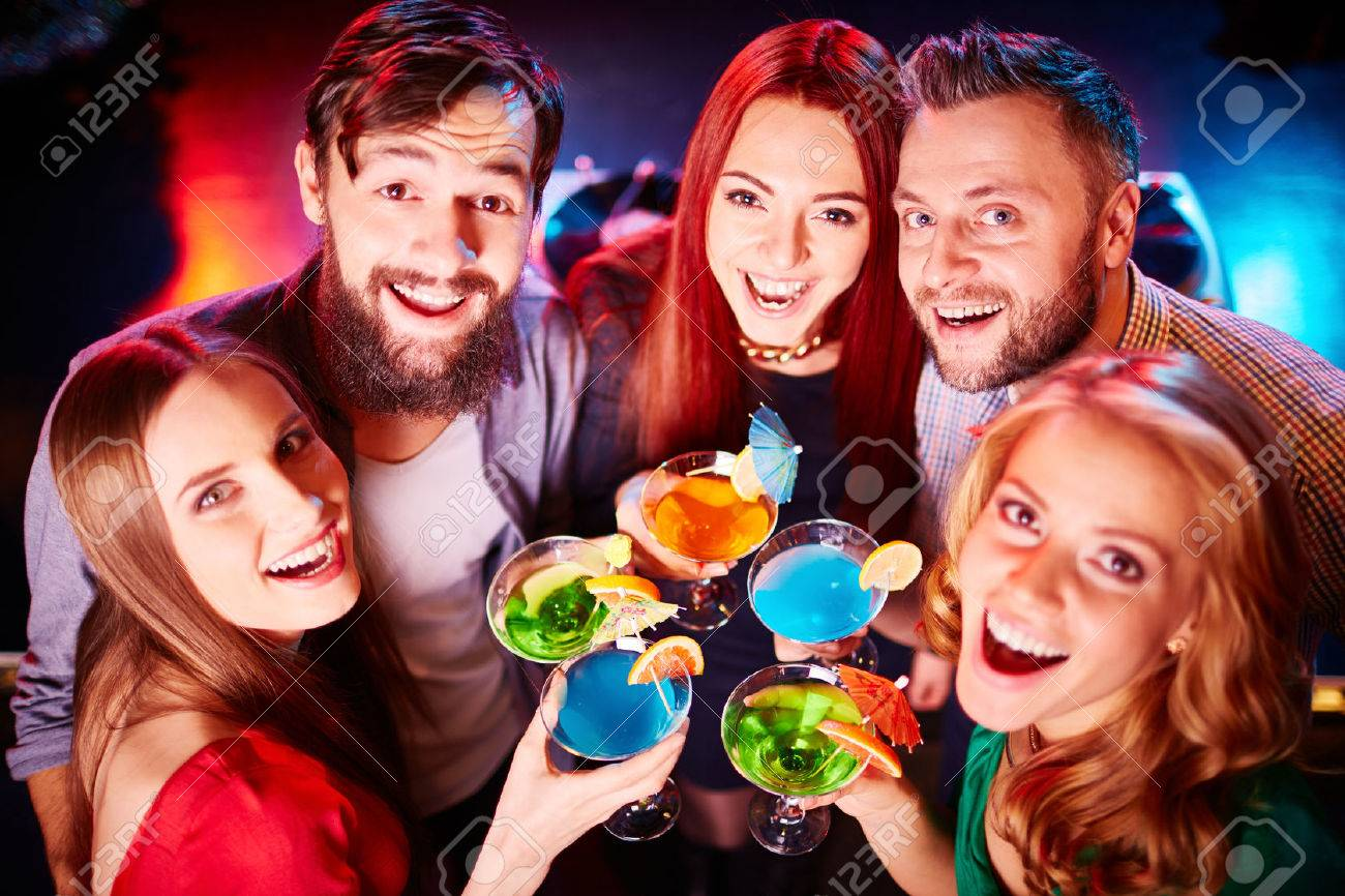 Ecstatic guys and girls toasting at party and looking at camera Standard-Bild - 45607278