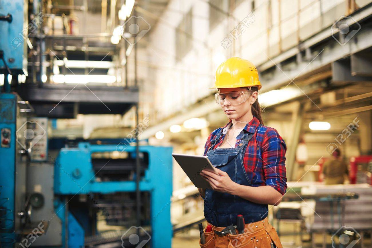 Woman in protective clothing using touchpad in factory Stock Photo - 50498889
