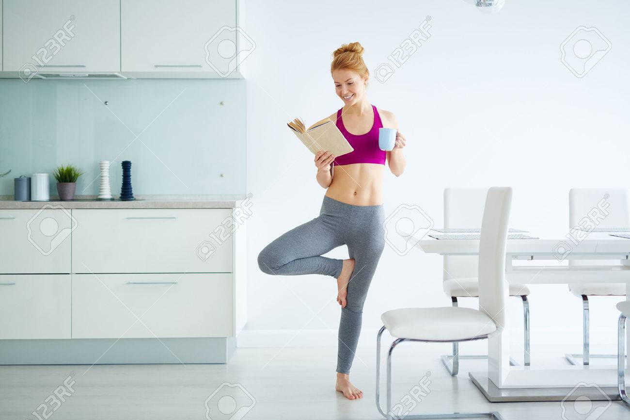 Young active woman with cup of tea and book practicing yoga in the kitchen Stock Photo - 51067253