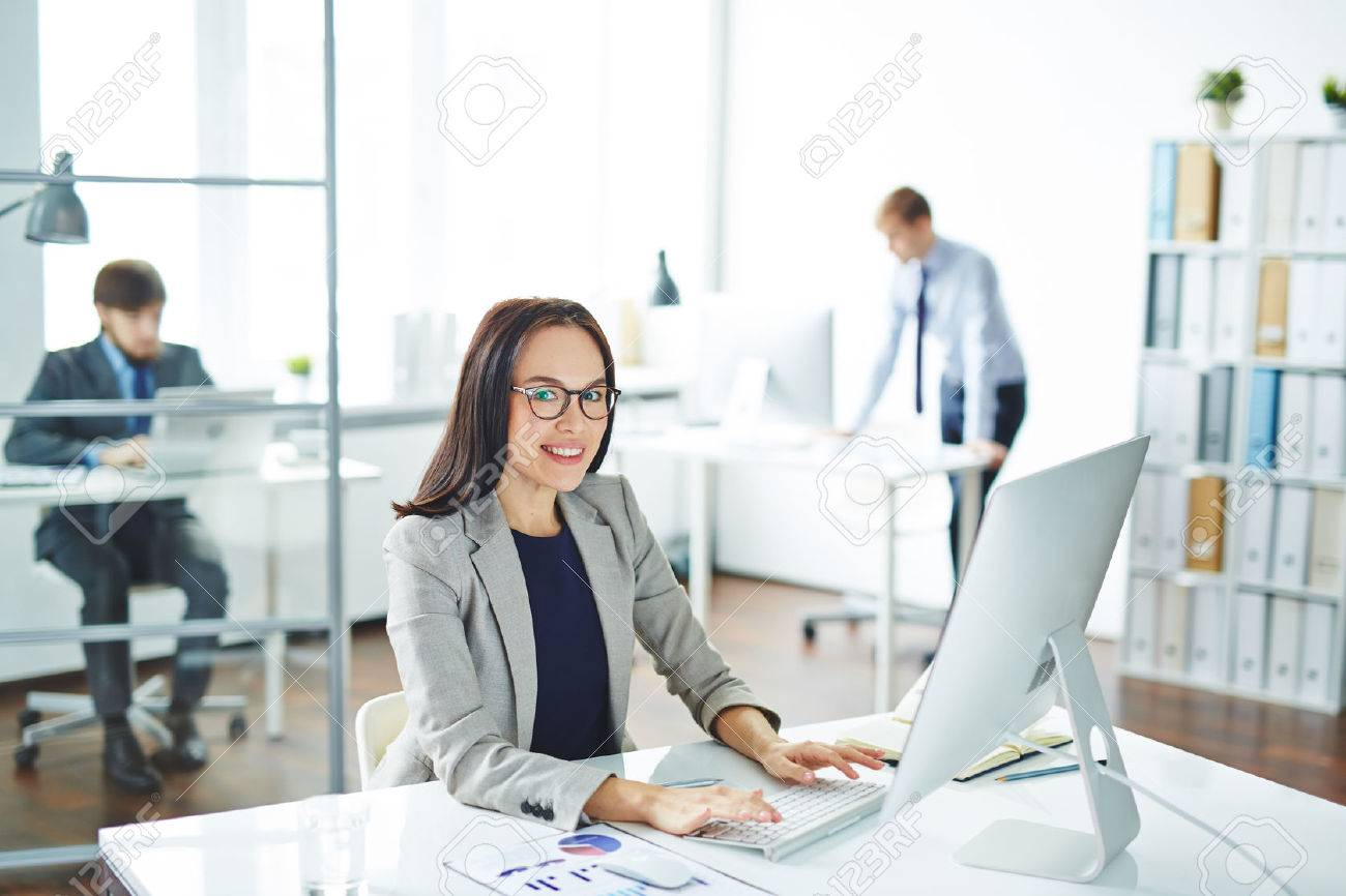 Pretty secretary looking at camera at workplace in front of computer Stock Photo - 52075616