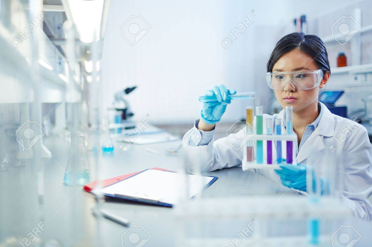 Female assistant analyzing fluids in flasks in scientific laboratory Stock Photo - 52075732