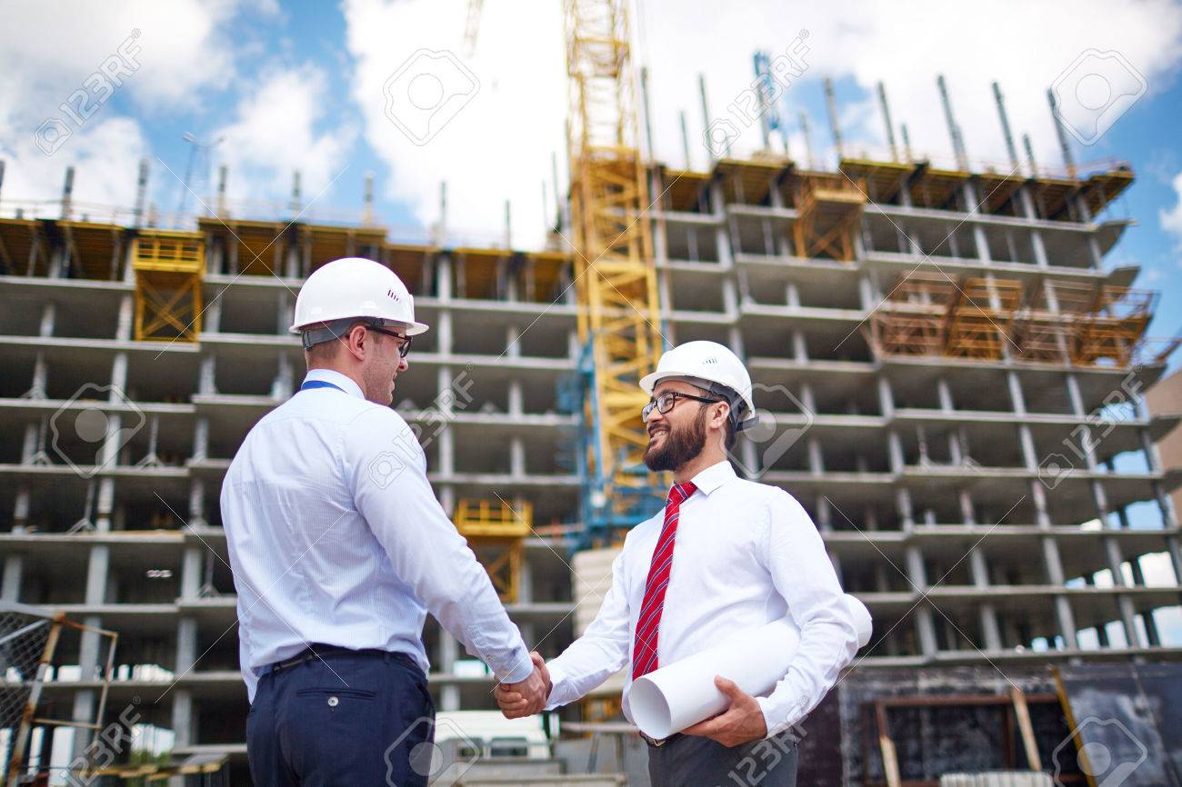Two young partners handshaking on background of building structure - 52075953
