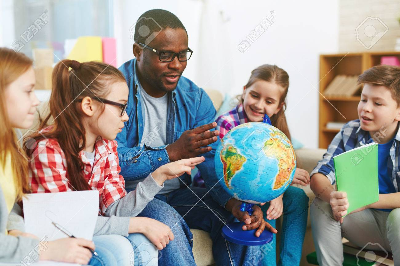 Group of preschoolers studying our planet on globe Stock Photo - 52077204