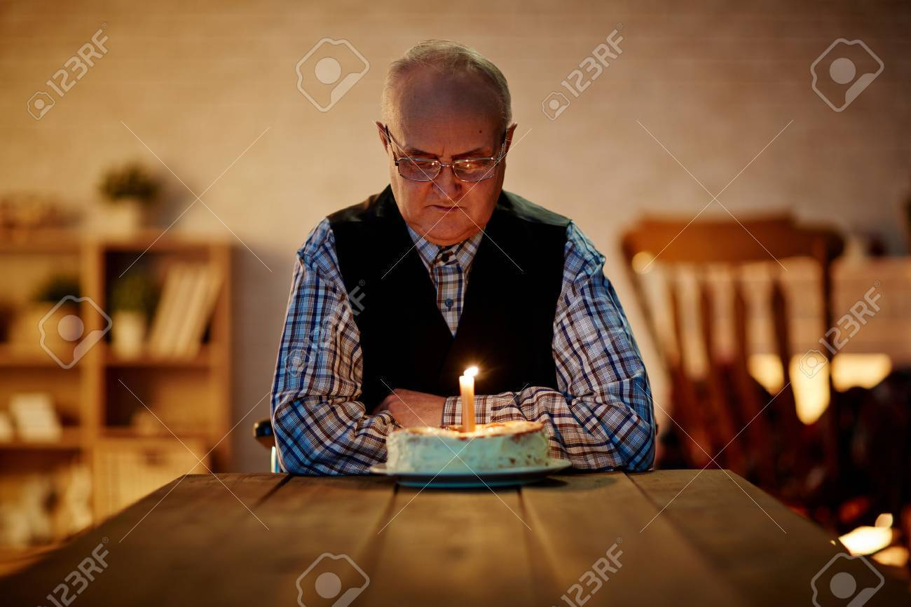 Mature Man Looking At Birthday Cake With One Candle Stock Photo