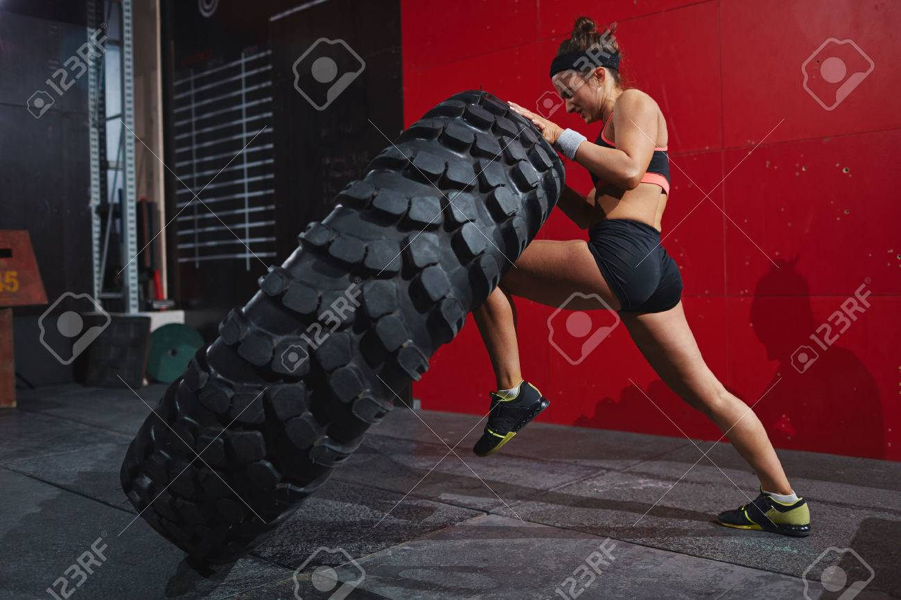 Active woman in sportswear flipping tyre in gym Stock Photo - 52293630
