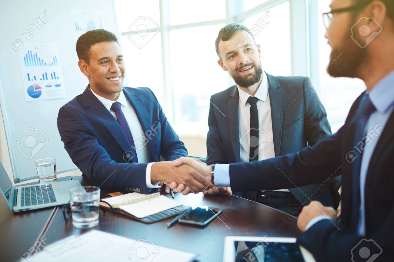Businessmen shaking hands during a meeting - 52936021