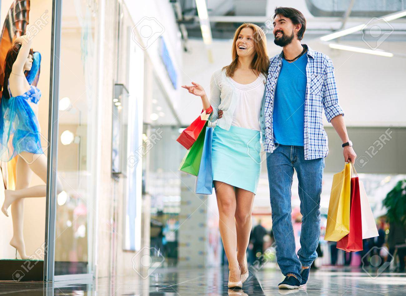 Beautiful couple walking through the mall and carrying shopping bags Stock Photo - 52936133