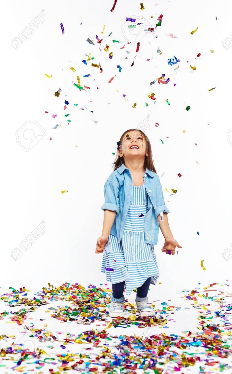 Cute little girl under falling confetti Stock Photo - 53427938