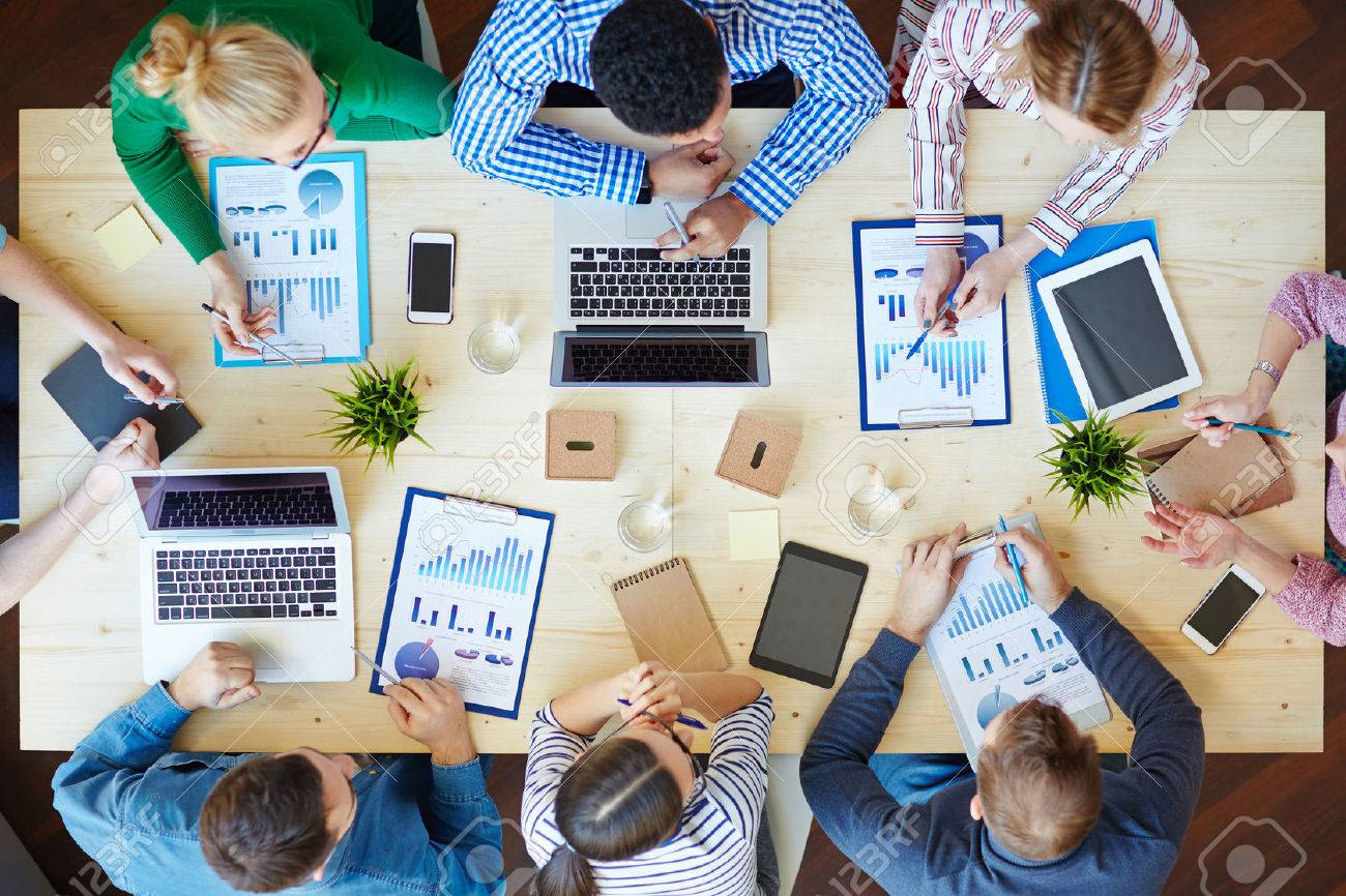 Above view of business team sitting around table and working Stock Photo - 53428558