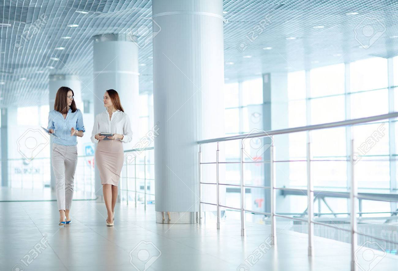 Two young businesswomen talking on business issues Stock Photo - 53768761