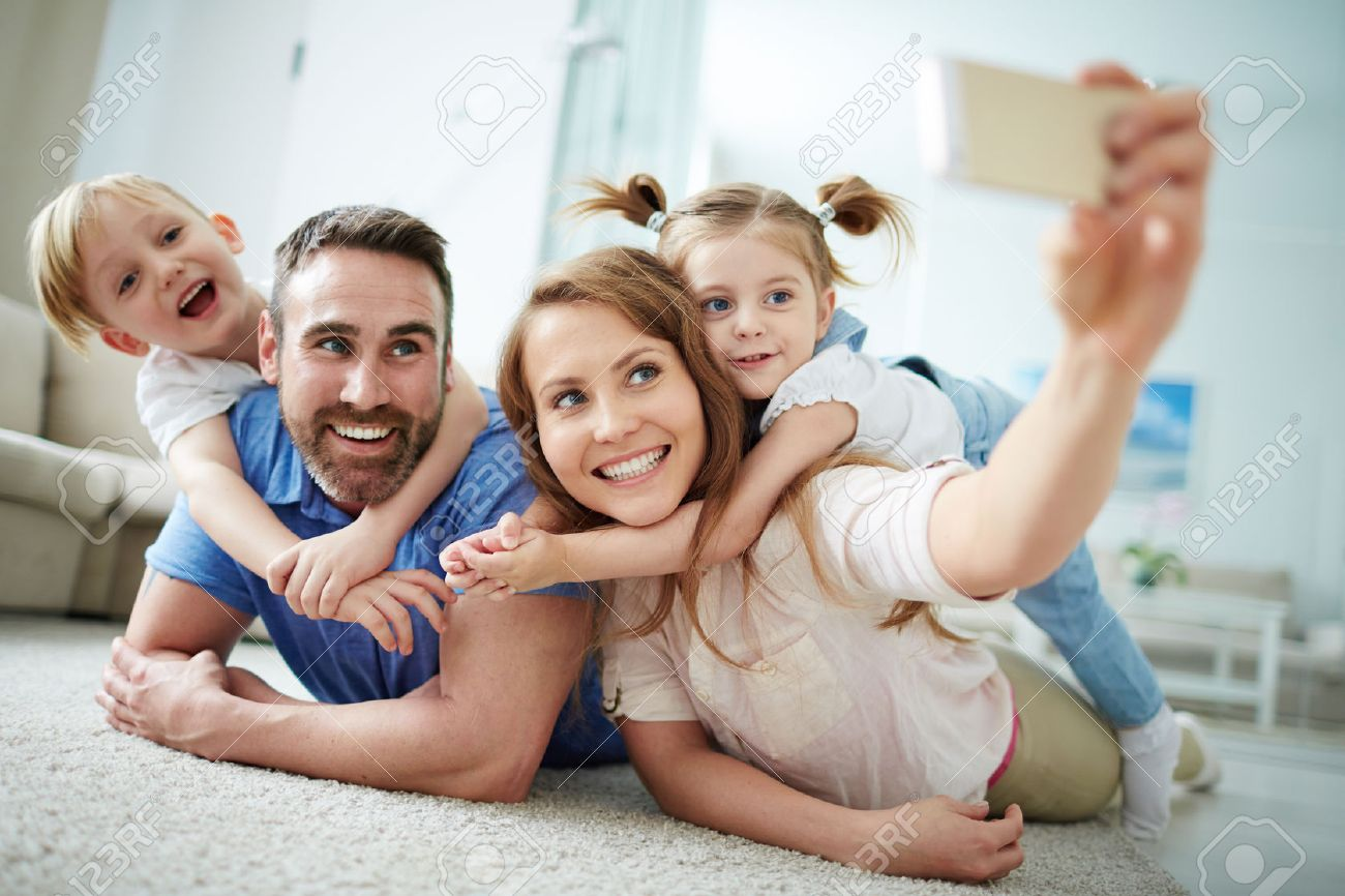 Happy young family taking selfie on the floor at home Stock Photo - 53864099