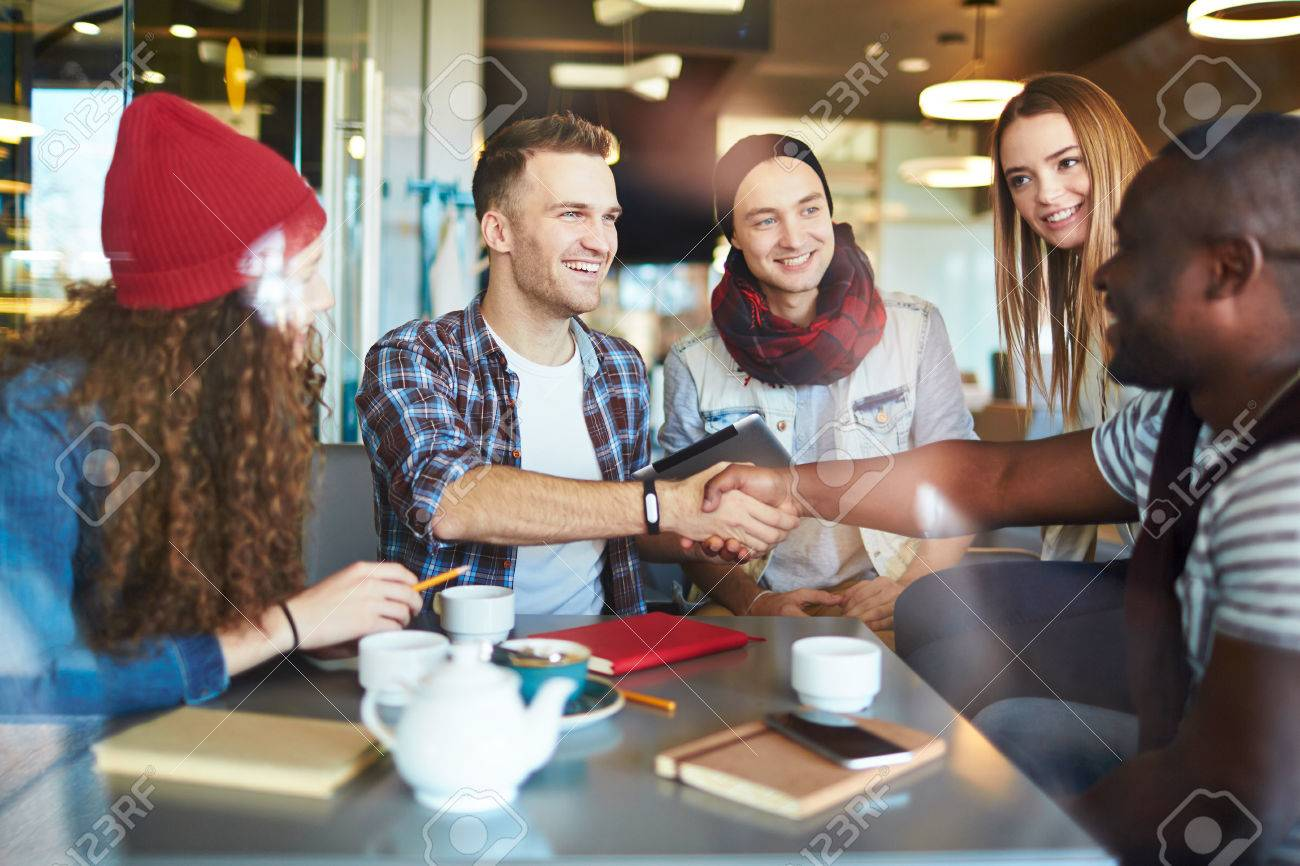 Smiling men shaking hands with his friend Stock Photo - 53879589