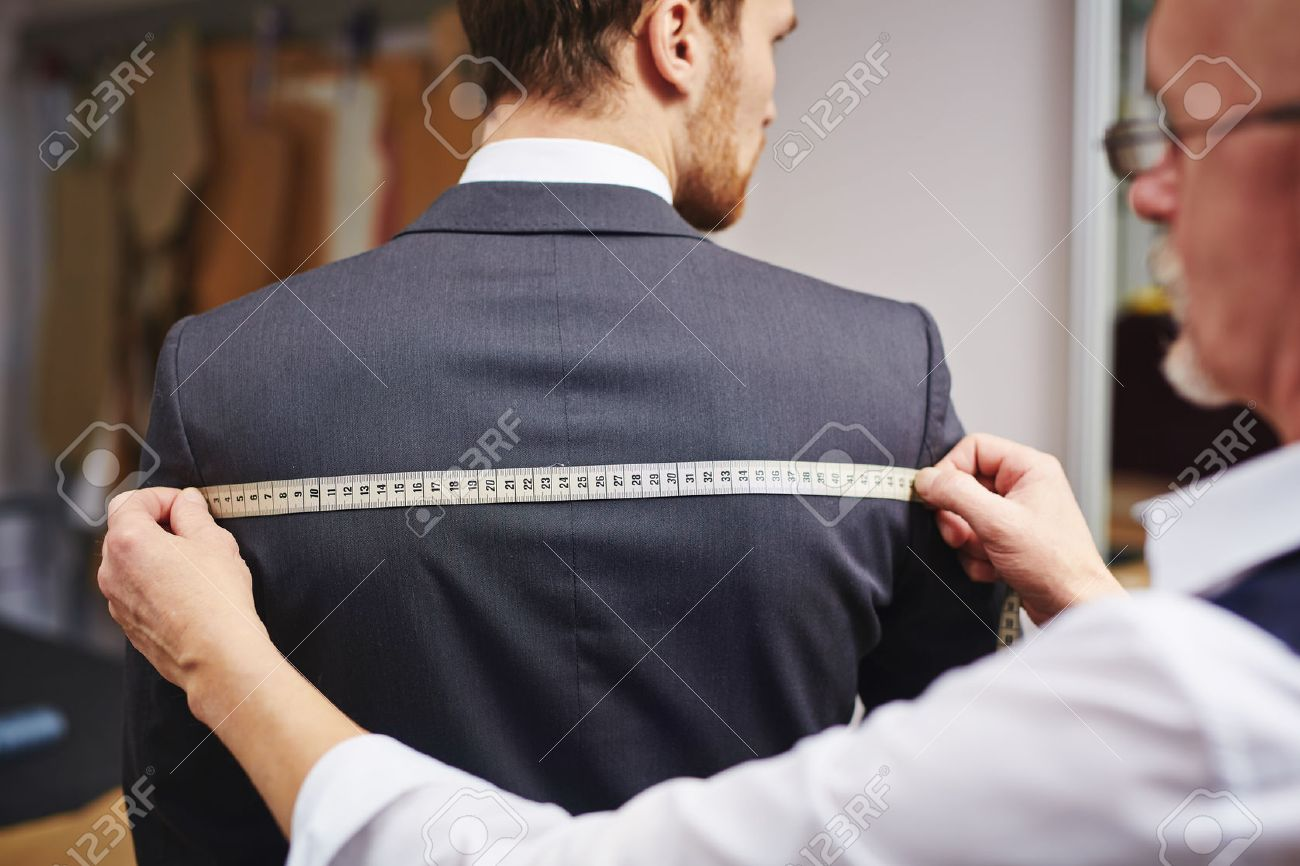 Mature tailor measuring back of jacket worn by his client - 54234634