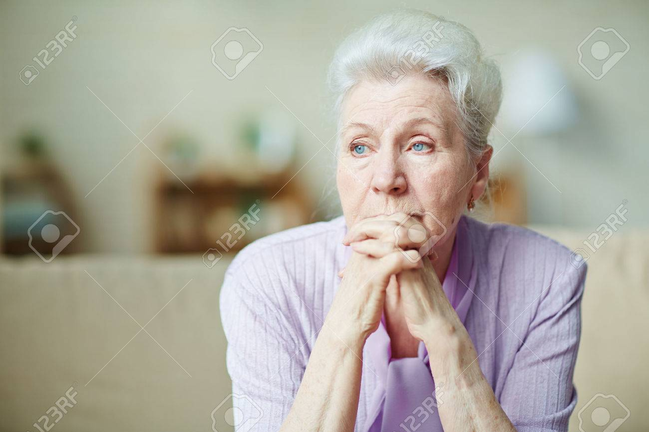 Elderly woman keeping hands by her lips Stock Photo - 54474225