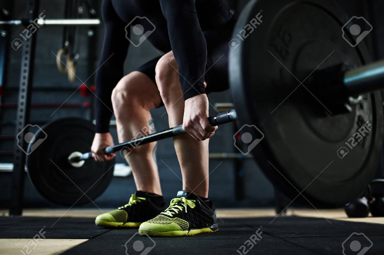 Active young man training with barbell in gym - 54721092