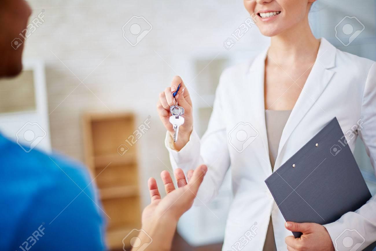 Woman realtor giving keys to a man - 55298304