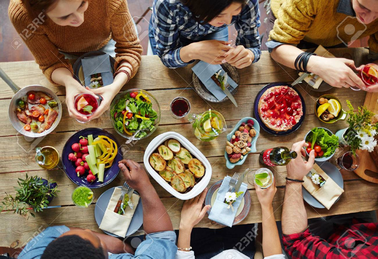 Intercultural friends eating tasty food by dinner Stock Photo - 55722766