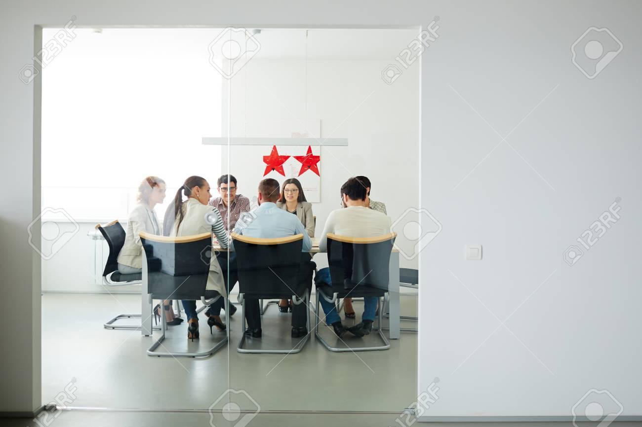 Groupe de jeunes gestionnaires réunis par la table dans le bureau