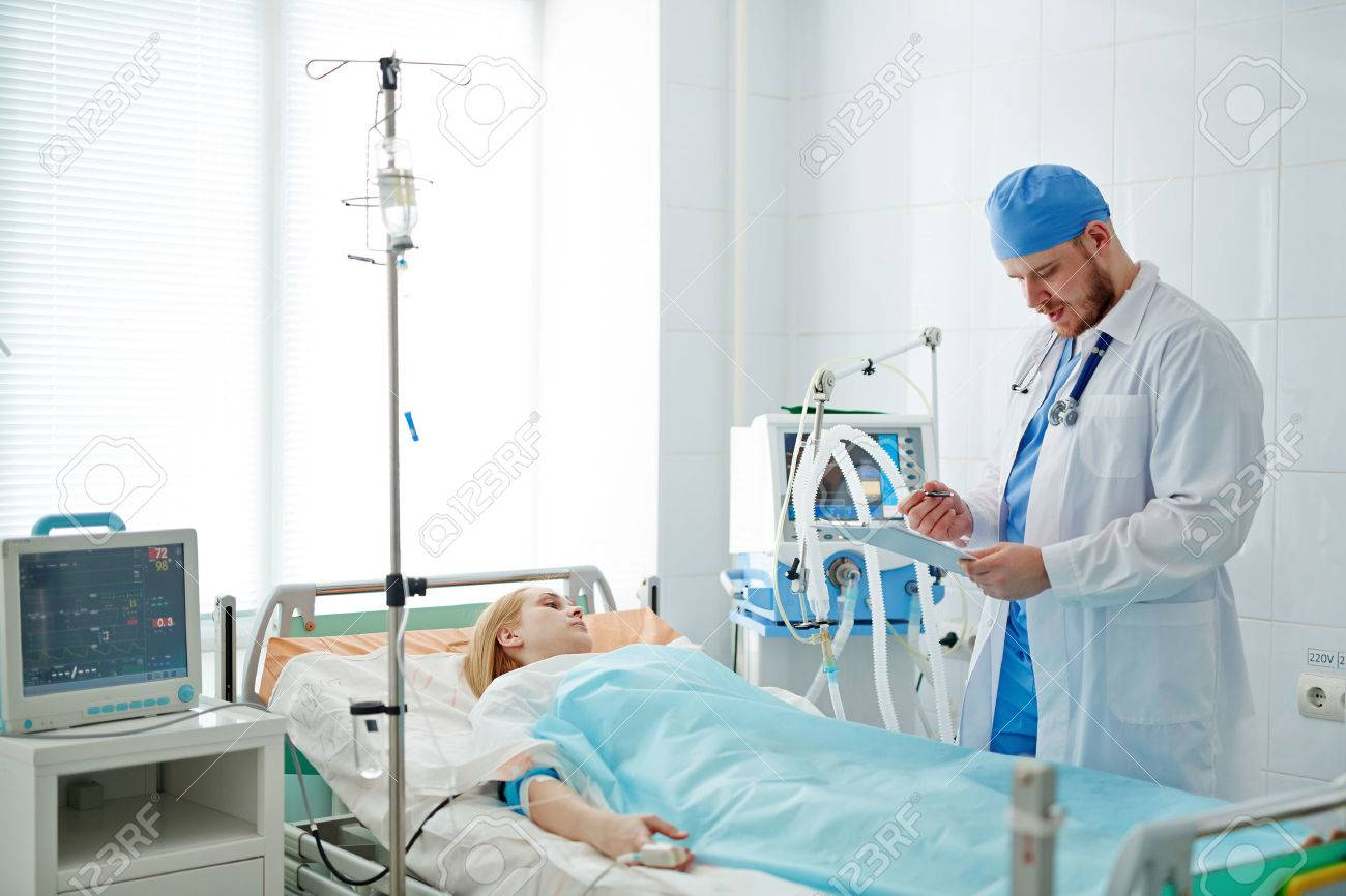 Doctor standing at bed with patient in intensive care - 56140256