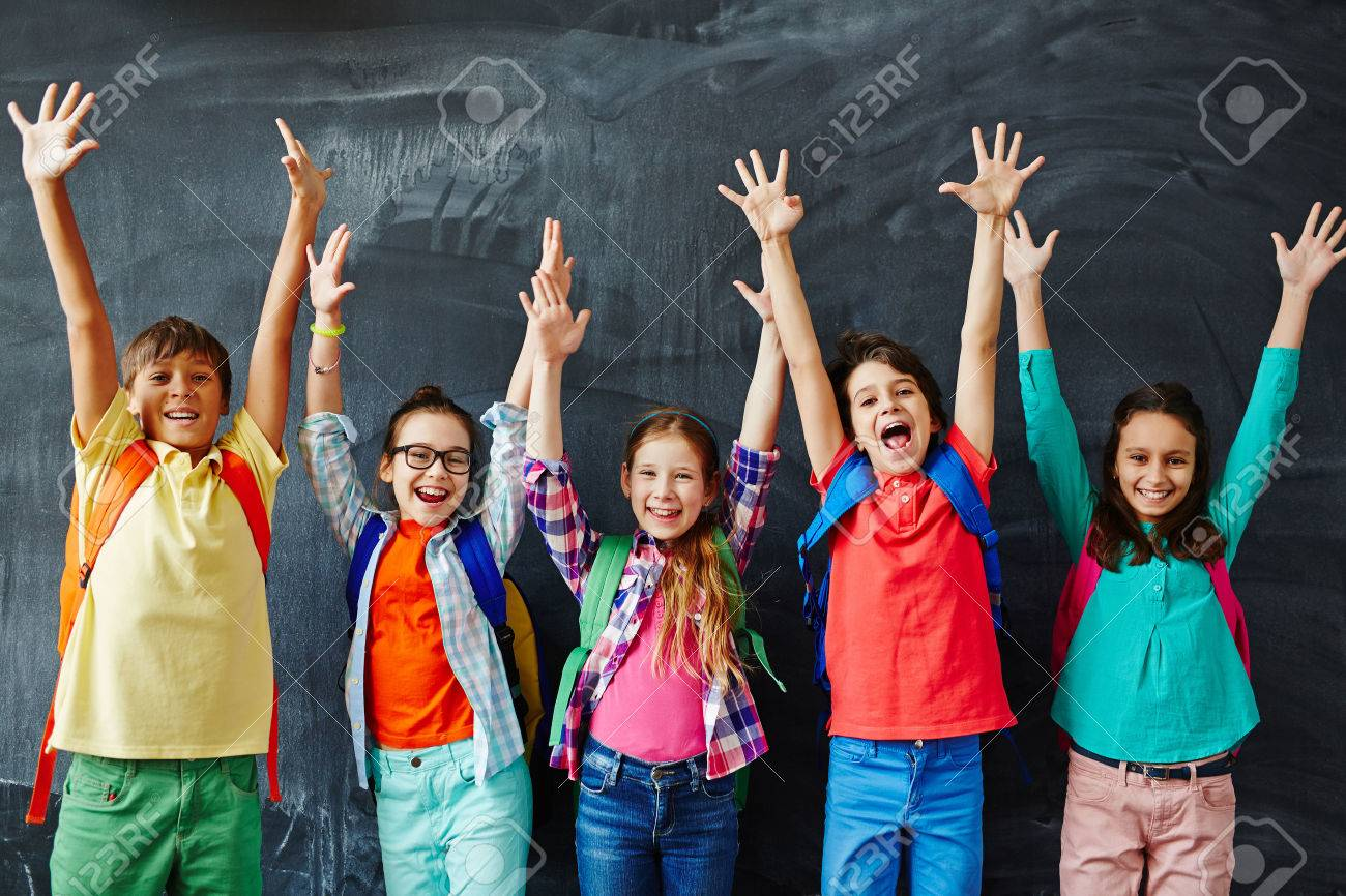 Excited schoolchildren standing with hands up Stock Photo - 58053767