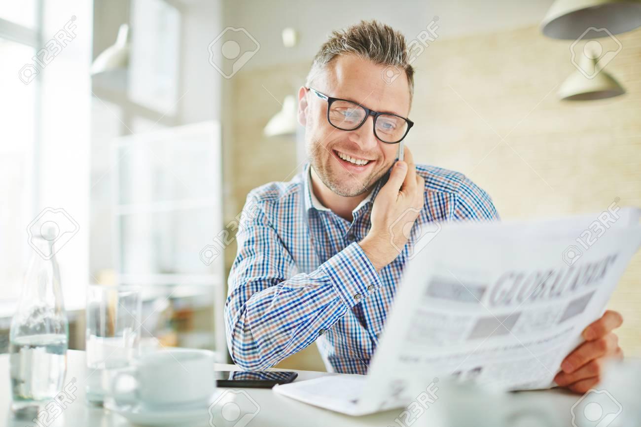 Employé heureux avec le journal d appel dans le bureau banque d