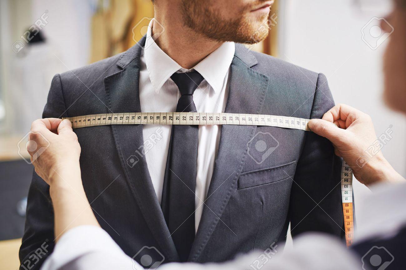 Tailor measuring front of businessman jacket - 58463490