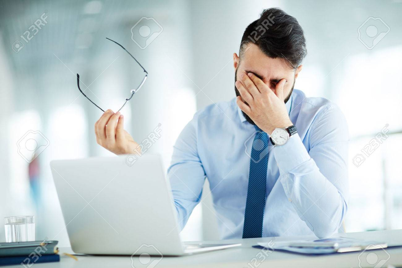 Businessman rubbing eyes at laptop Stock Photo - 58944785