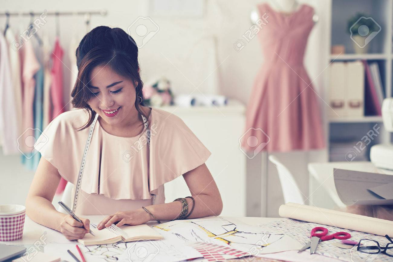 Smiling charming young woman seamstress drawing sketches and patterns at the table Standard-Bild - 59967452